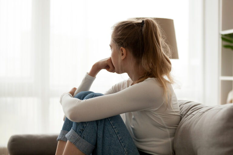 Teen girl looking out window