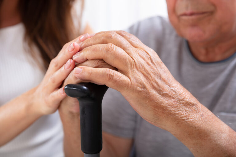 Woman with hand on elderly man's hand