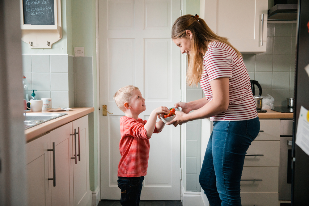 Mother with young child having snack in kitchen