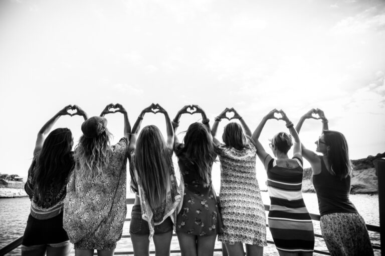 black and white photo of friends making hearts with hands