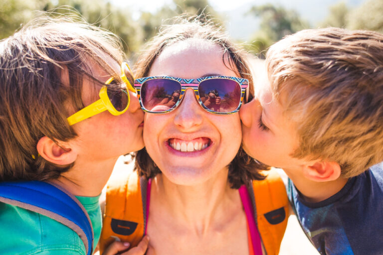 Little boys kissing mom on cheeks