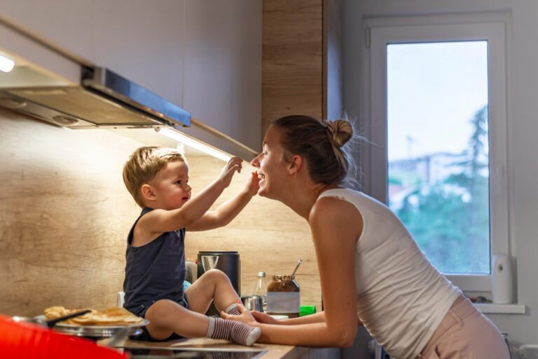Mom at kitchen stove with child