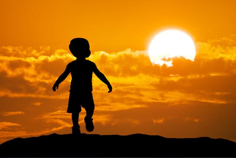 Little boy silhouette in sunset