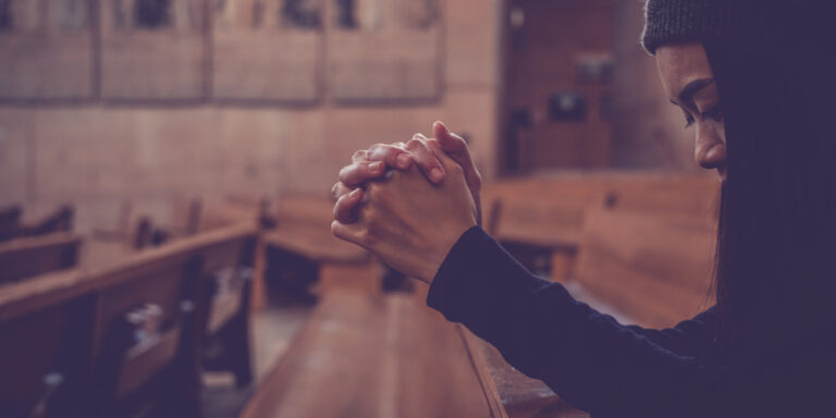 Woman in church pew praying