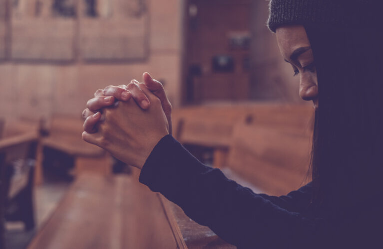 Woman in church pew praying
