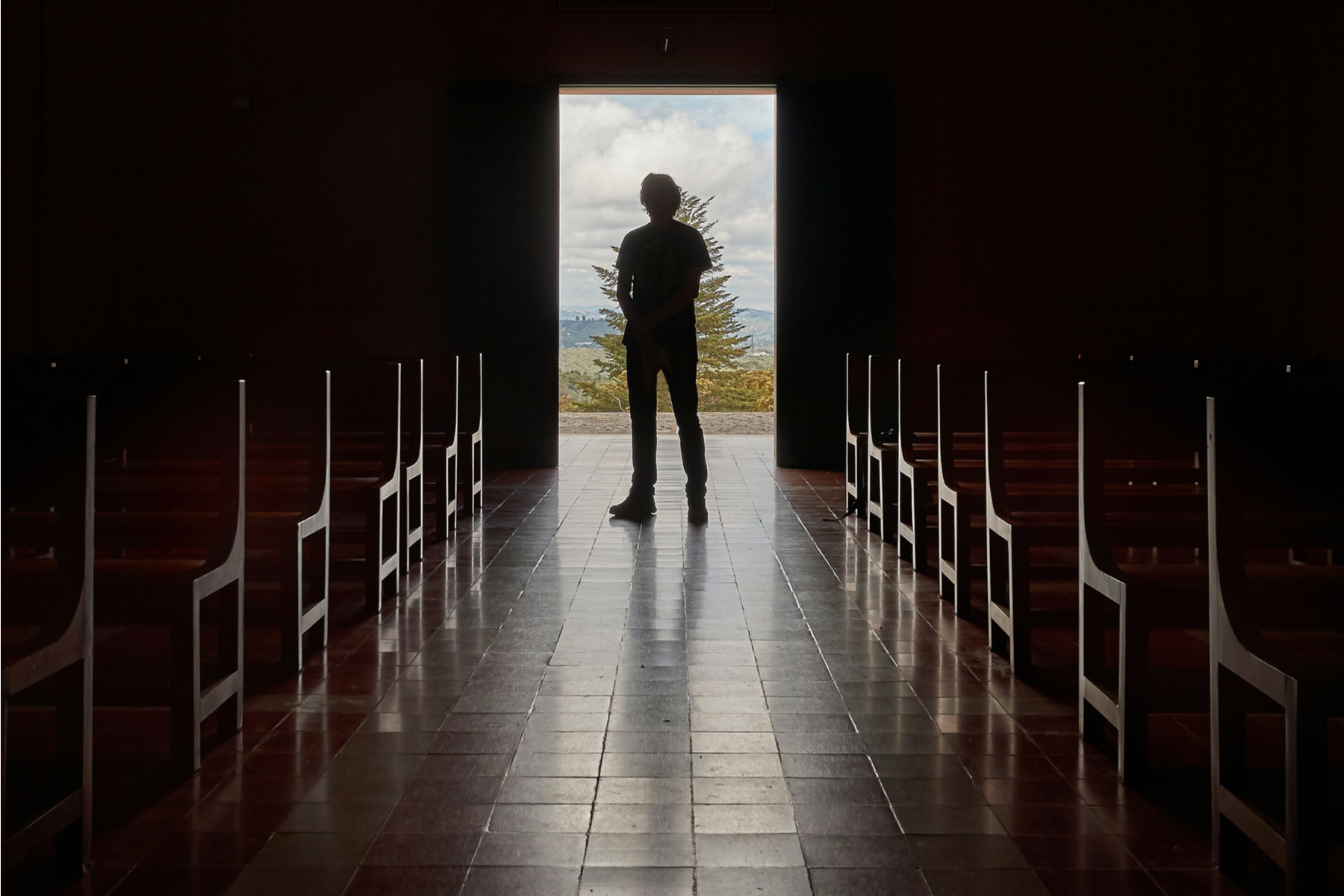 Man standing at end of church hallway