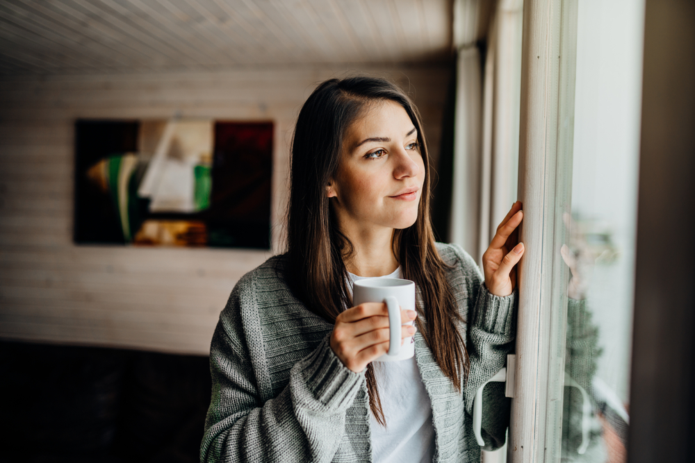 Woman with coffee cup looking out window