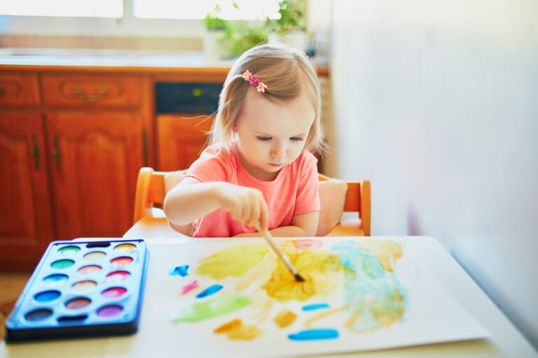 Child painting at home with watercolors
