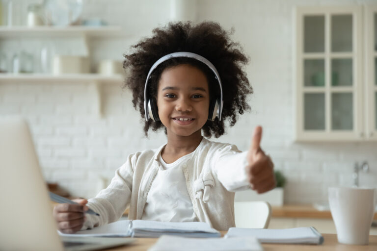 child with headphones giving thumbs up