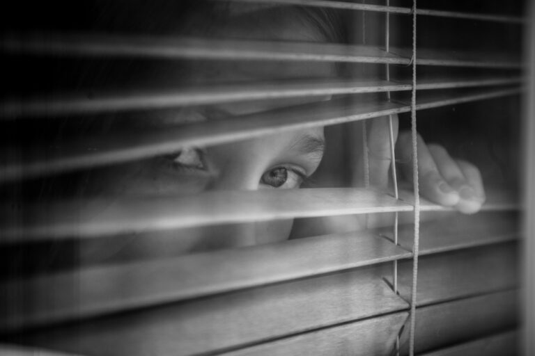 Sad eyes looking out window blinds