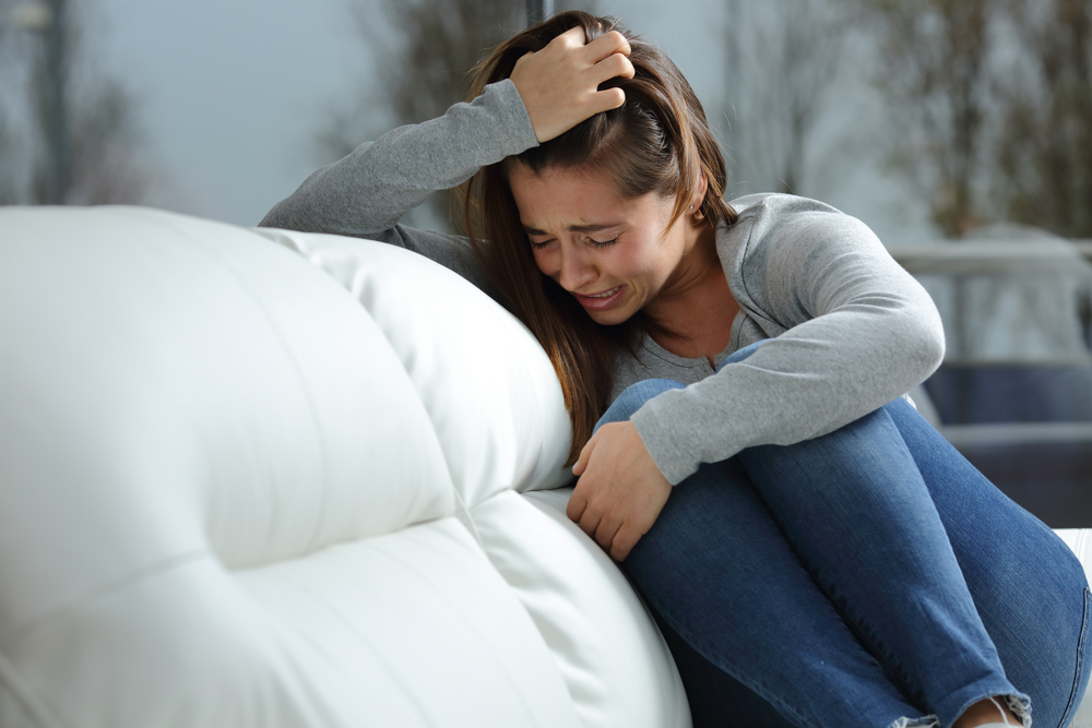 Crying woman on couch