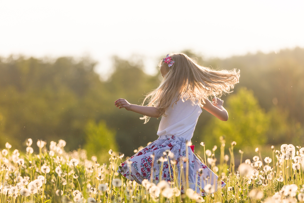 Girl twirling in field