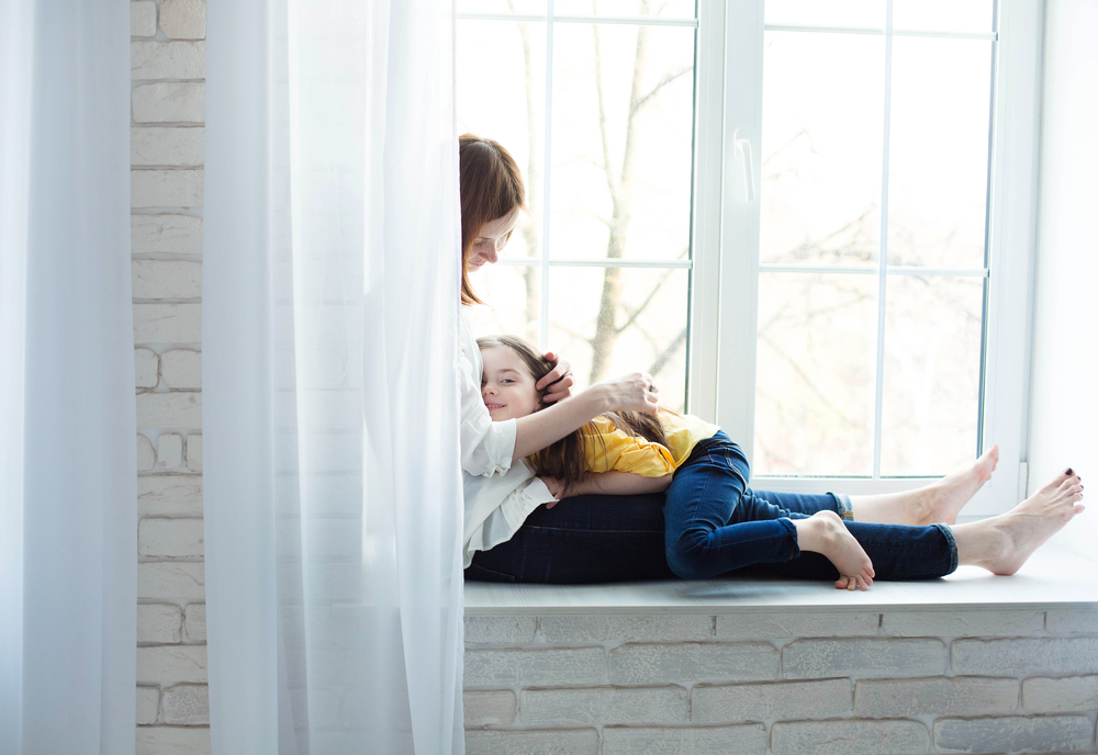 Mother sitting with child in window