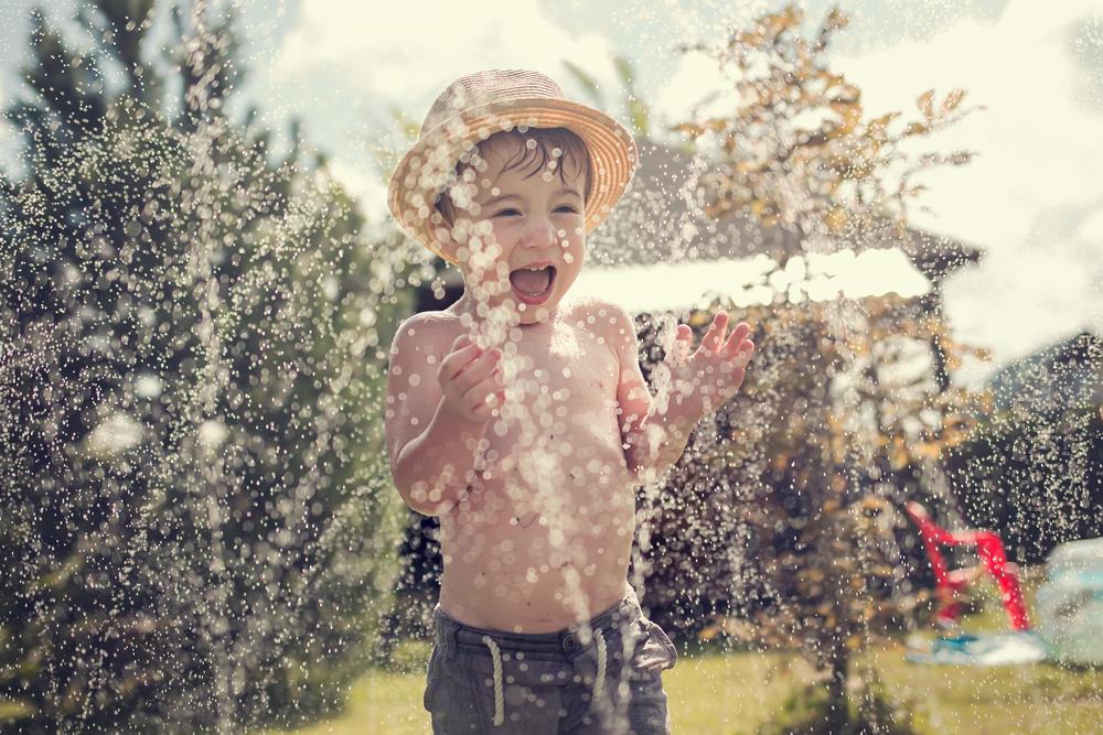 Little boy in sprinkler