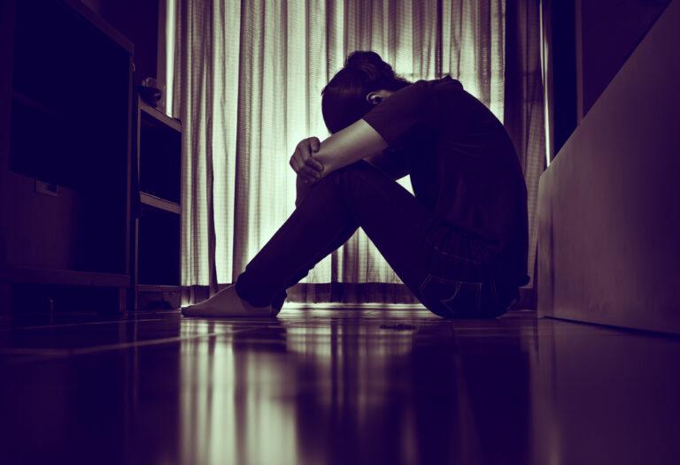 Sad woman hugging knees