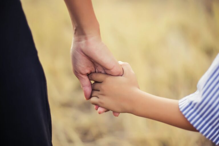 Mother and child hold hands