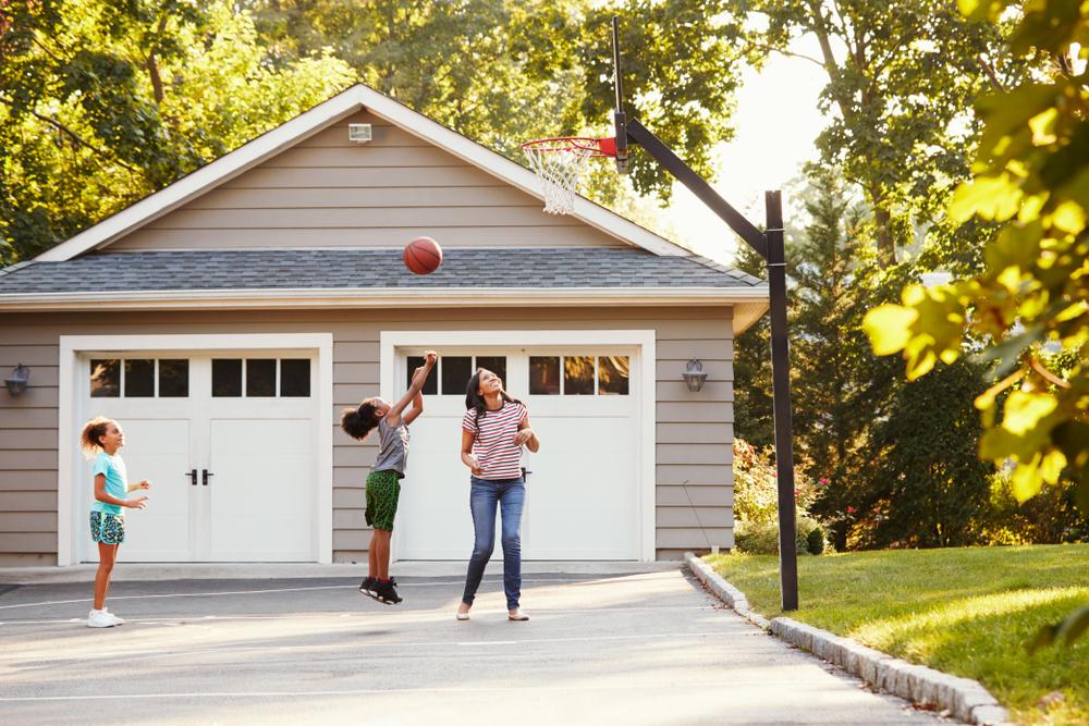 Family playing basketball outside home