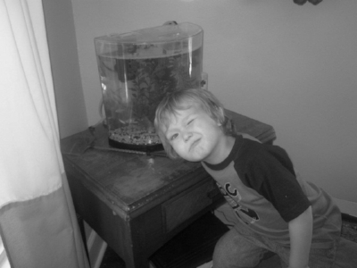 Little boy winking next to fish tank, black-and-white photo