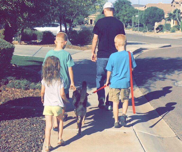 Family walking dog, color photo