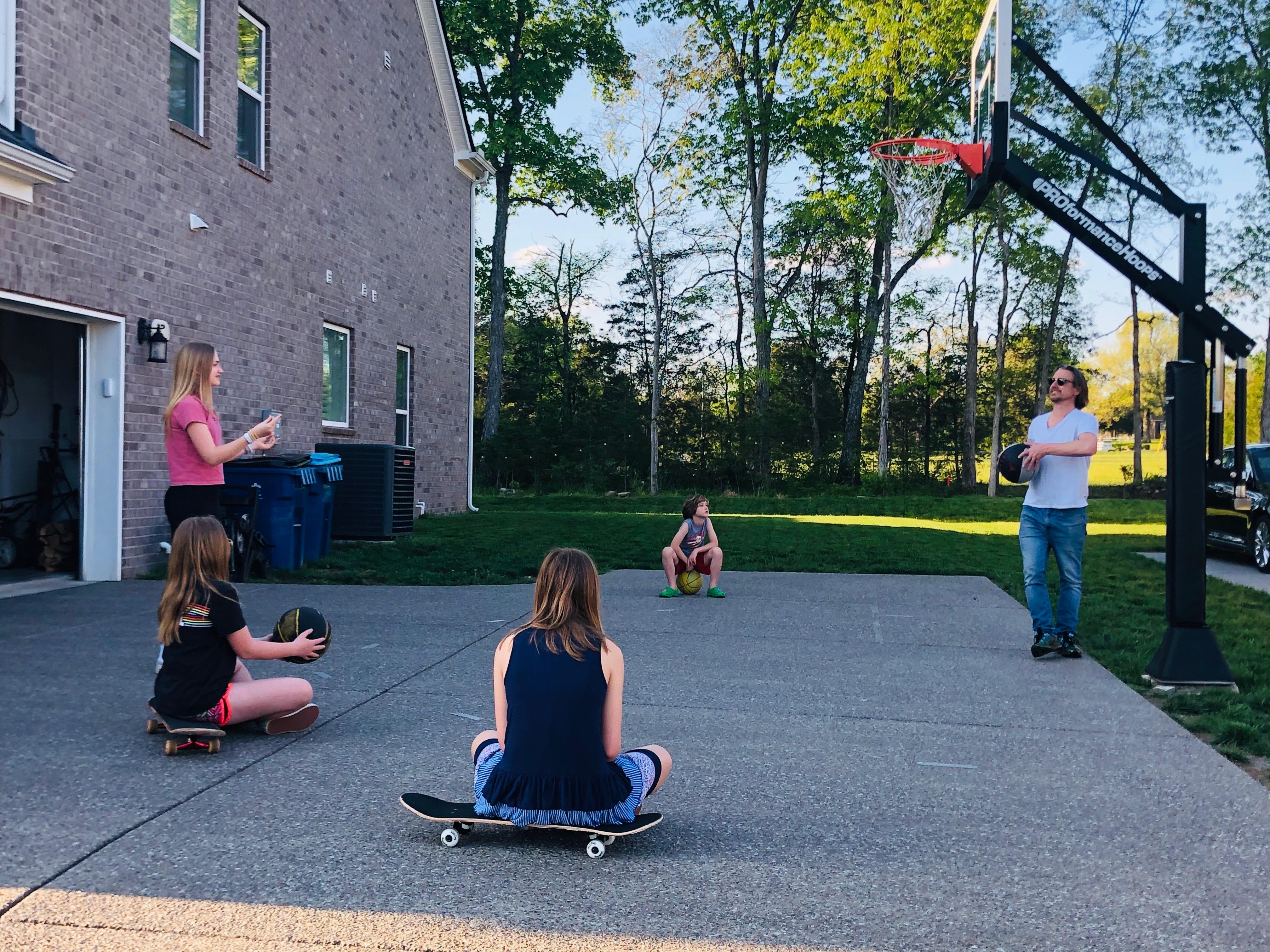 Family playing basketball outside