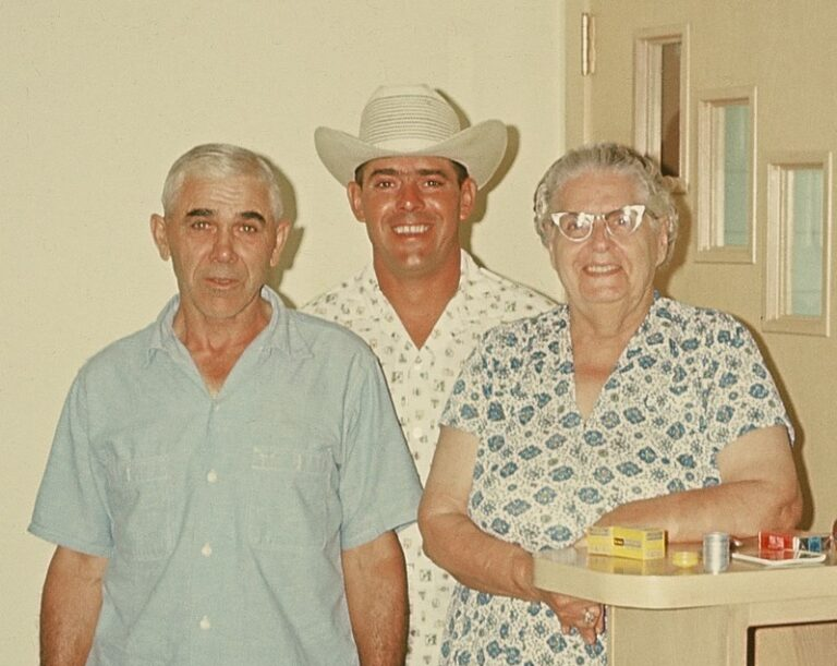 Two men and woman smiling, color photo