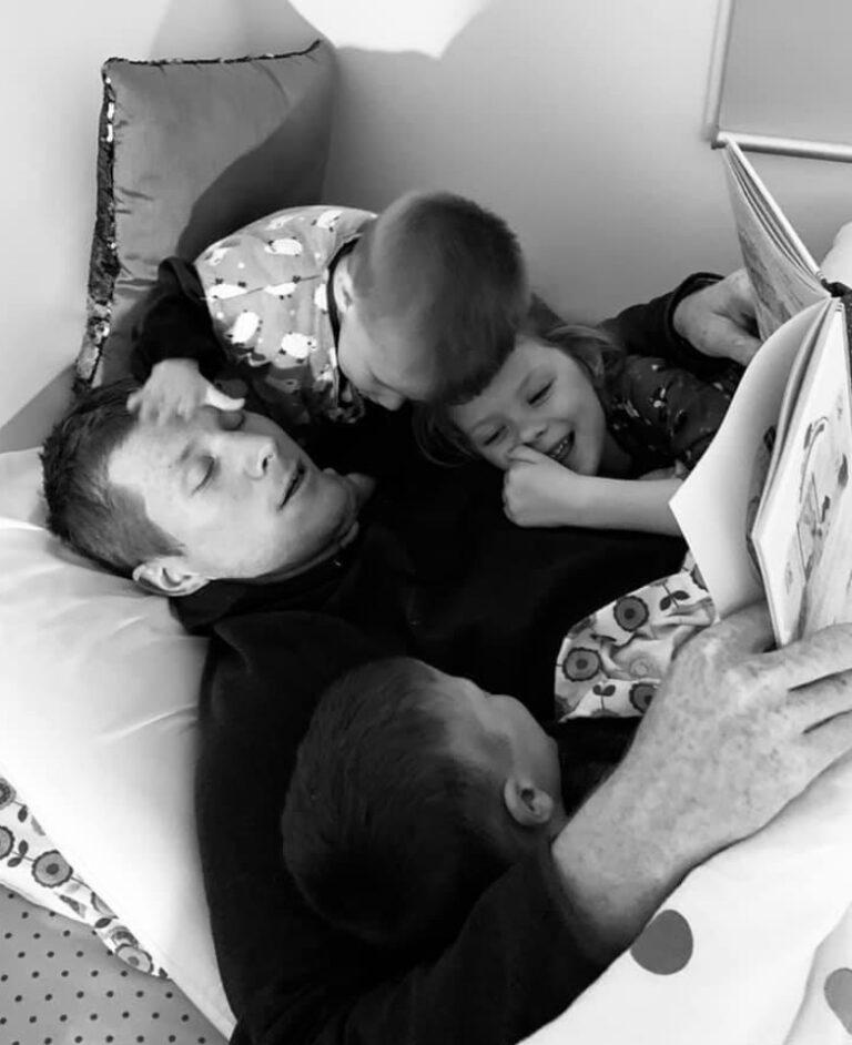 Daddy with three kids on him, black-and-white snapshot