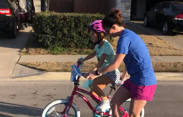 Mom helping daughter on bike