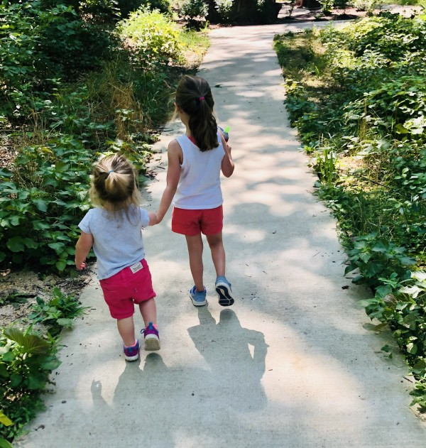 Two little girls walking down sidewalk