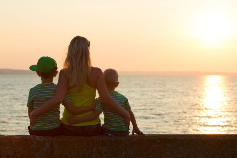Woman with two kids by beach
