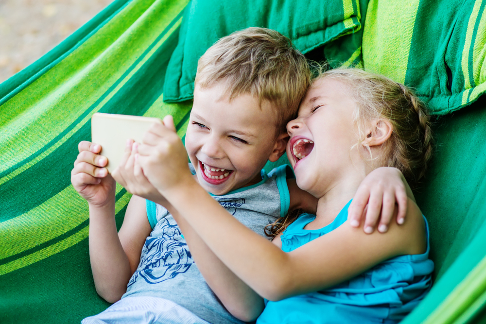 Two kids laughing together in hammock