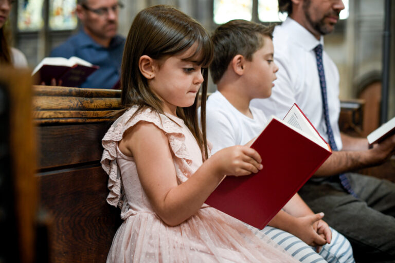 Little girl holding hymnal in church