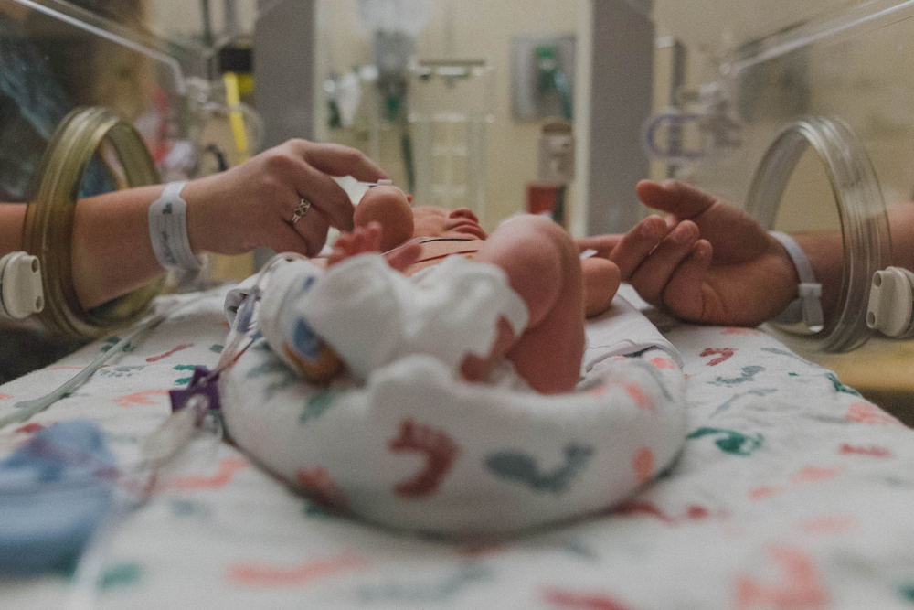Baby in NICU parents holding hands