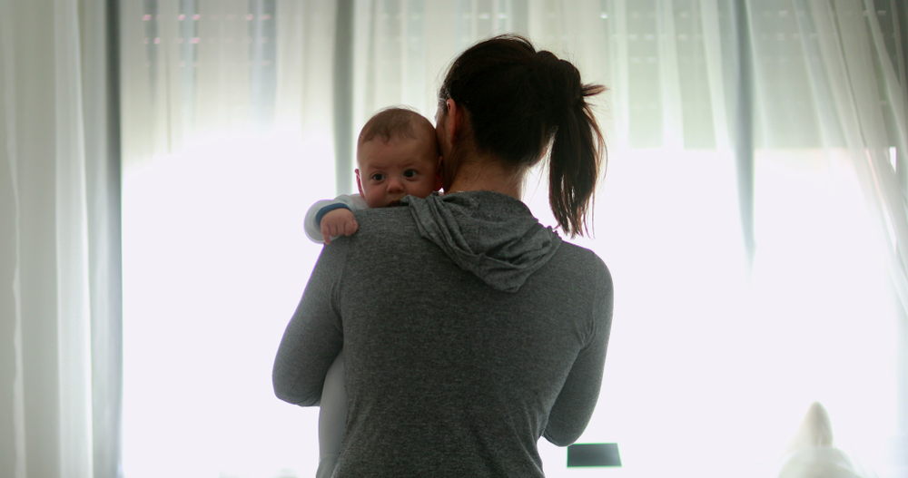 Mother holding baby on shoulderr