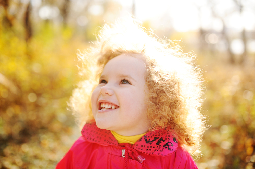Little girl looking up outside in sunshine