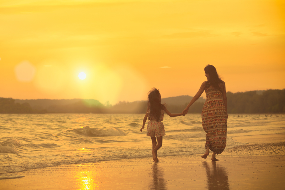 Mom and daughter walk on beach