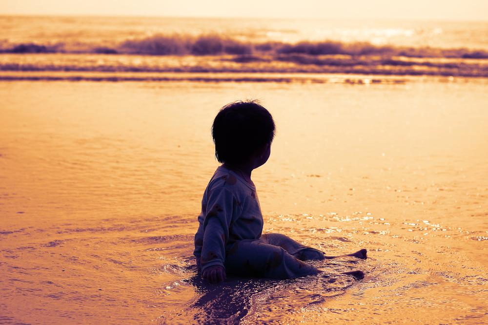 Child sitting in water on beach