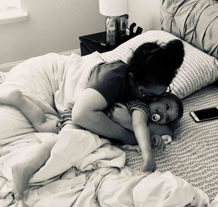 Mother hugging child on bed