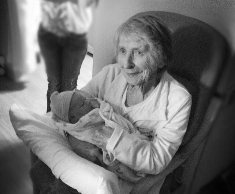 Grandmother holding newborn, black-and-white photo