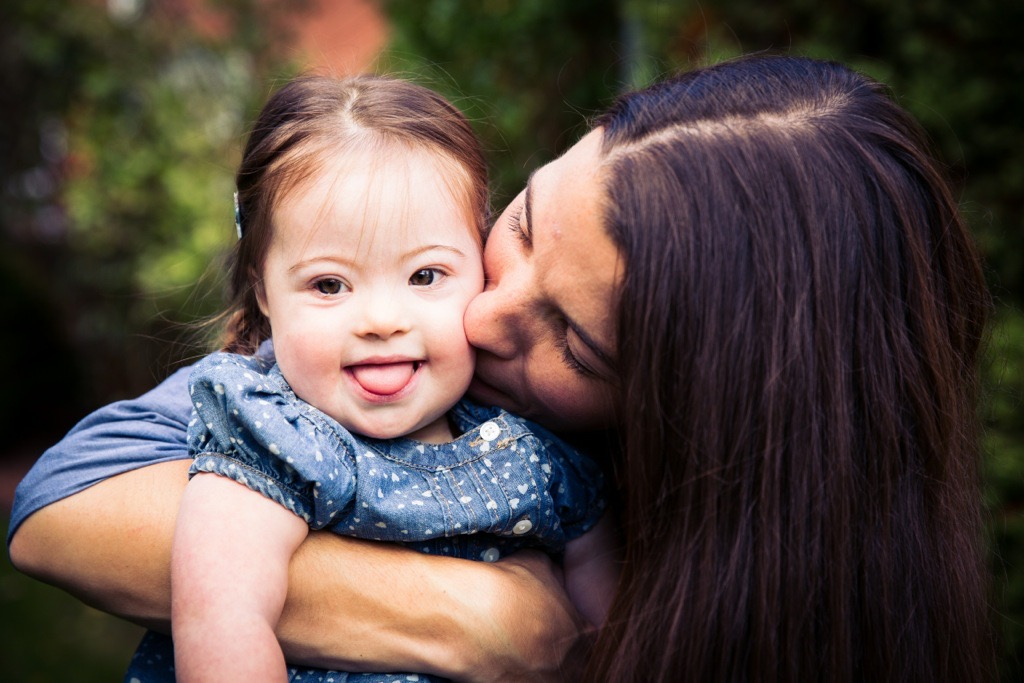 Mother kissing daughter with Down syndrome