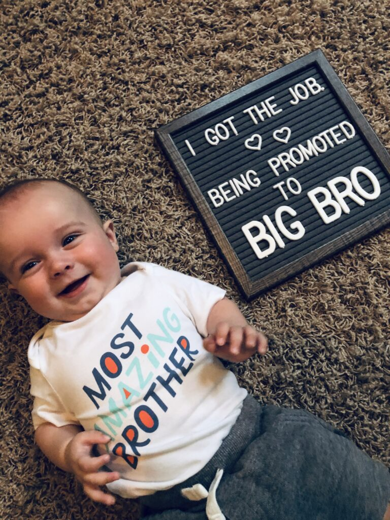 Baby boy next to pregnancy announcement sign, color photo