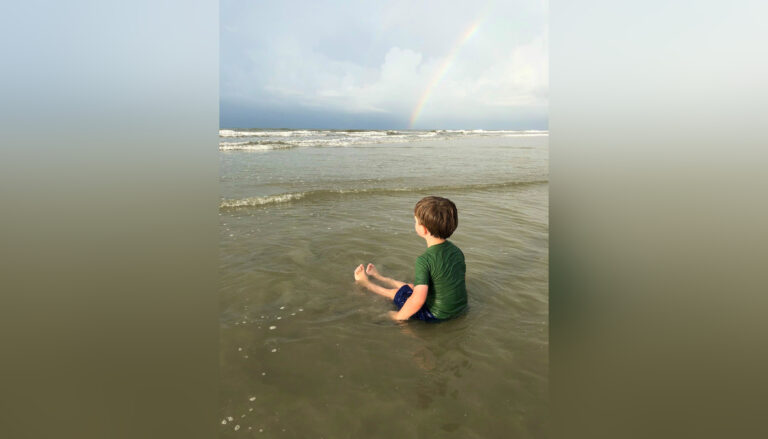 Little boy sitting on beach with rainbow in distance