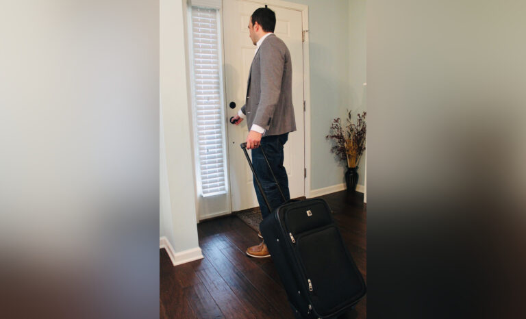Man leaving home with suitcase
