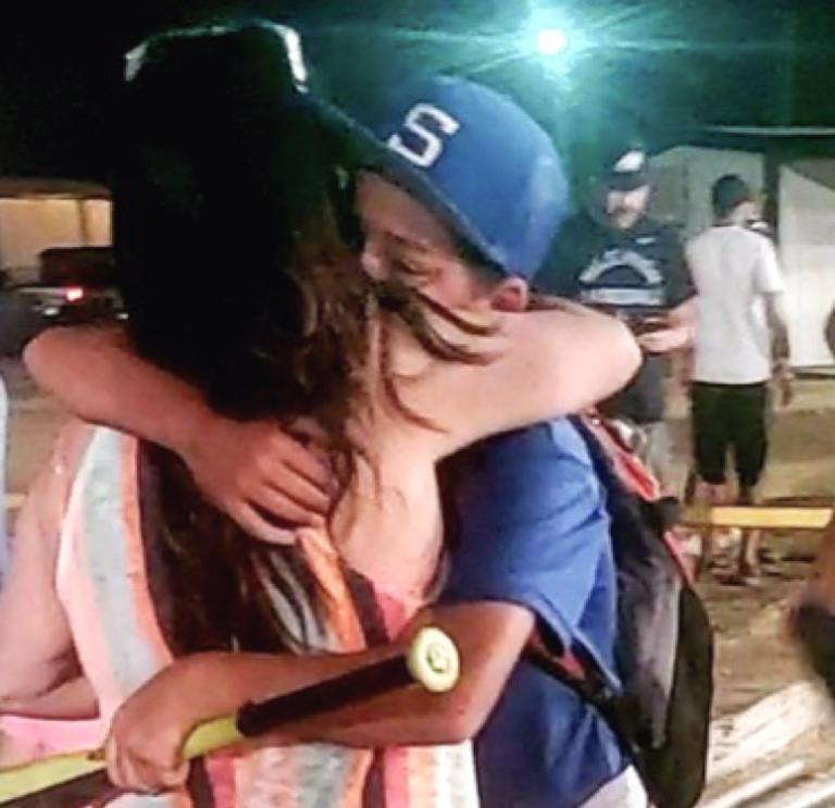 Mom hugging son after baseball game