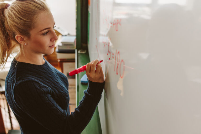 Young woman teacher at white board