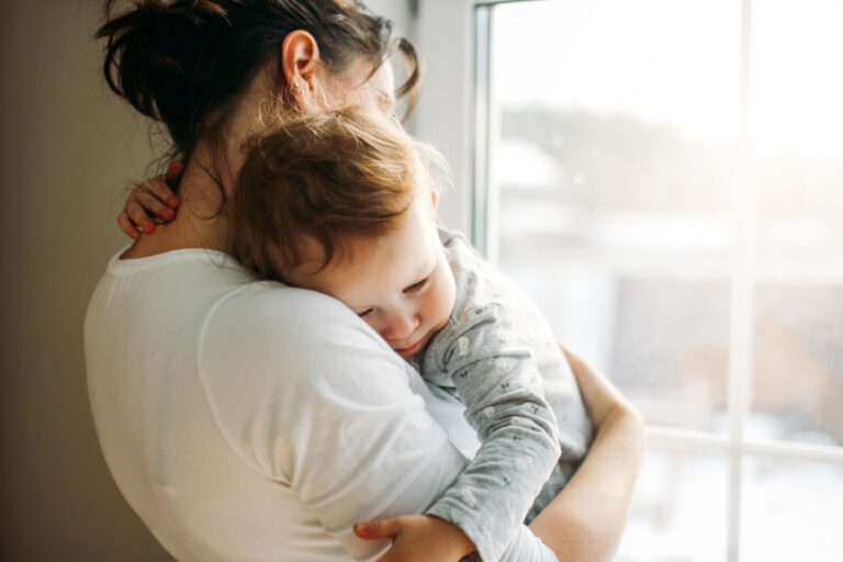 Mom holding baby by window