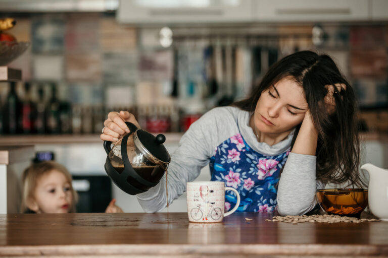 Tired mom pouring coffee on table