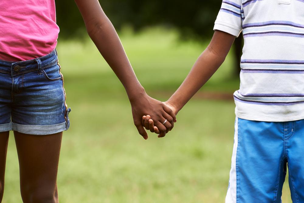 Two Black children hold hands
