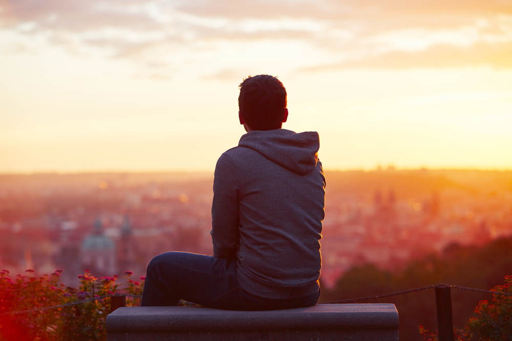 Young man looking over city at sunrise