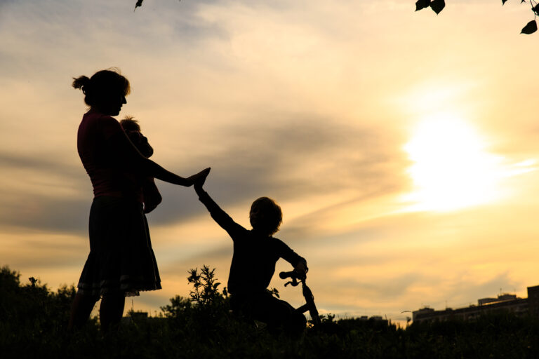 Mother and kids silhouette at sunset
