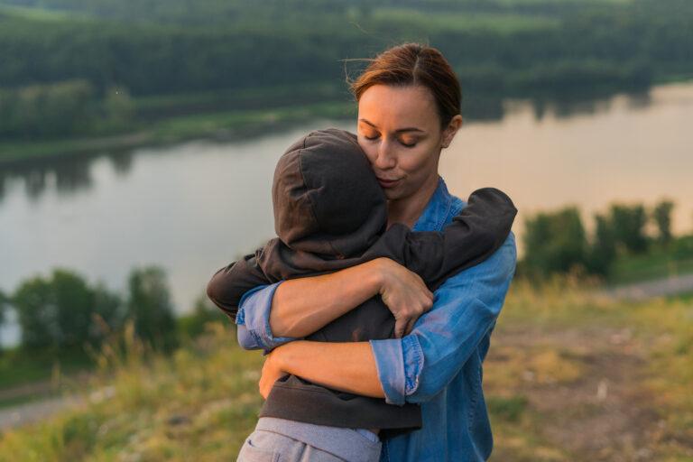 Mom hugging son outside